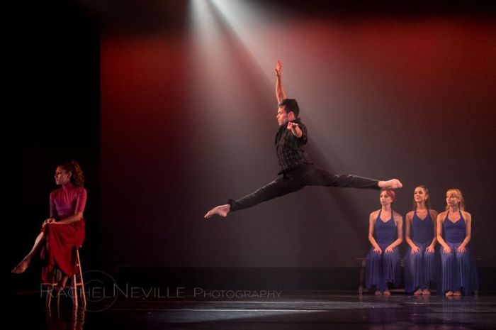 male dancer jumping over seated women jete stage live performance photo by rachel neville