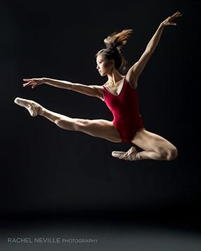 muscular dancer powerful jump red leotard ponytail